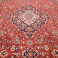 Classic handknotted red ground with dark blue medallion and border Persian Carpet handmade in the central Iranian city of Kashan.