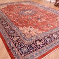 Handmade, handknotted Persian Mahal Carpet of blue medallion design set against a terracotta field with floral arrangements.
