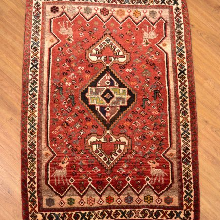 Charming red Persian tribal Qashqai Rug with medallion design and cute deer motifs in the corners.