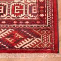 Narrow size Persian Turkoman Carpet with repeating design of dyrnak yamoud guls on a red background.