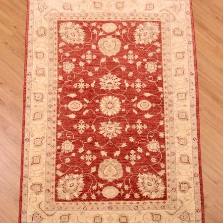 Red ground handknotted floral Afghan Rug of Ziegler design.