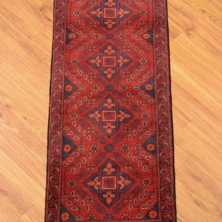 Handmade, handknotted Afghan Khan Mohamadi Kharack strip with 4 gul emblem design on a browny-red field.