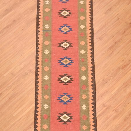 Handwoven Persian Qashqai Kilim Runner of 8 medallion design on a terracotta ground with a soft green border.