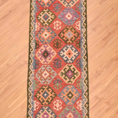Handwoven Afghan Veg Dye Kilim Runner of 14 gul design on a terracotta background made entirely from wool.
