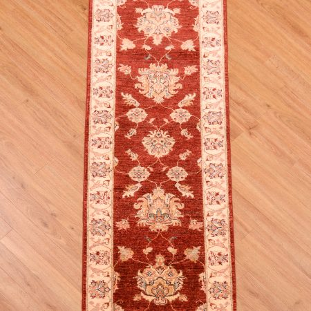 Handmade, handknotted Afghan Ziegler Strip of red background and beige border.