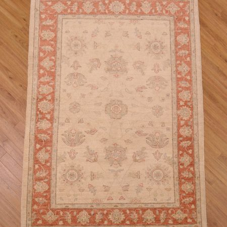 Handmade, hand knotted Afghan Ziegler design Rug made with ghazni wool pile and beige background and soft rust border.