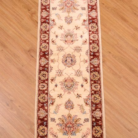 Handmade, handknotted Afghan Ziegler Runner with beige central field surrounded by rust red border.