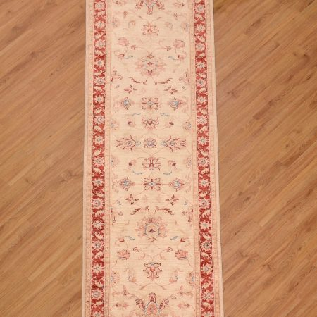 Handknotted Afghan Ziegler Runner of all over floral design on a beige background with red border. The wool pile has a silky sheen.
