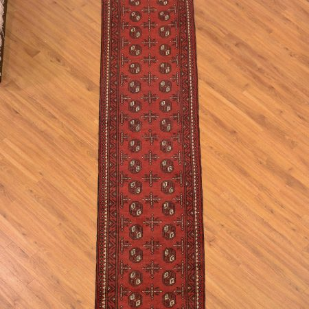 Narrow width classic Afghan Aqcha Bokhara Runner in traditional red colour scheme featuring 2 rows of Bokhara guls.