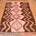 Vintage Ourika Rug with quirky pattern of 5 medallions of fabric material and fabric zigzags on a brown background.