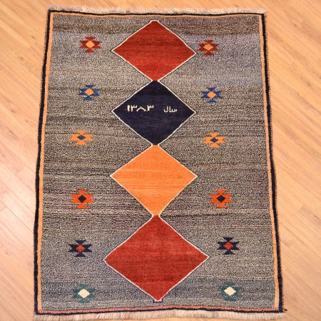 Handmade Persian Funky Gabbeh Nomad Rug with 4 diamond medallions and 10 smaller floral emblems on a speckled, salt & pepper background enclosed by a simple border. Also inscribed with a date 1383 / AD. 2005.