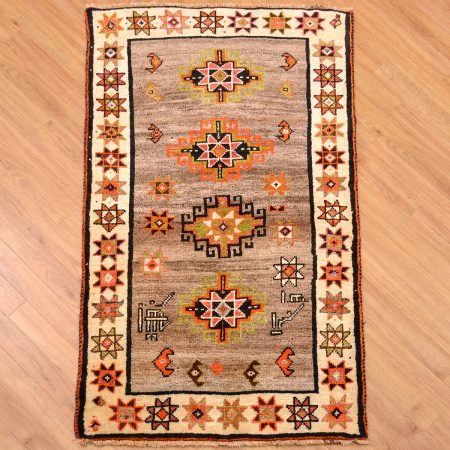Tribal handmade Persian Gabbeh Nomad Strip Rug of hand-knotted wool pile with 4 medallions on a grey background surrounded by a beige star motif border.