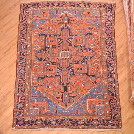 Early 20th Century handmade, hand-knotted wool pile, Persian Antique Heriz Carpet with bold medallion design set against a terracotta rust field with stunning blue corners surrounded by a navy blue border. Possibly made in the village of Karadja.