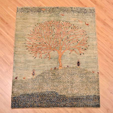 Handmade modern Afghan Pictorial Rug depicting a tree on a mountain scene set against a pale blue background.