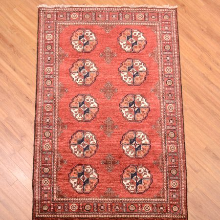 Handmade Afghan Ersari Rug with 10 gul pattern on a terracotta field.