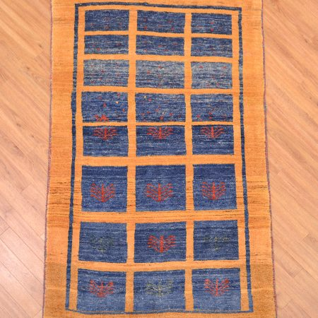 Handmade Persian Gabbeh Modern Rug with blue panel design against a mustard background.