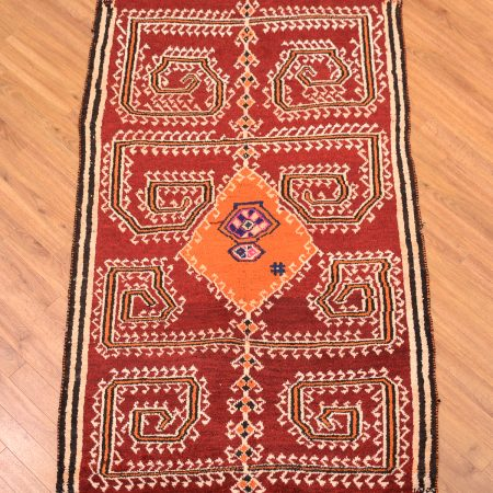 Hand-knotted Persian Gabbeh Tribal Rug with orange medallion and spidery pattern on a red field.
