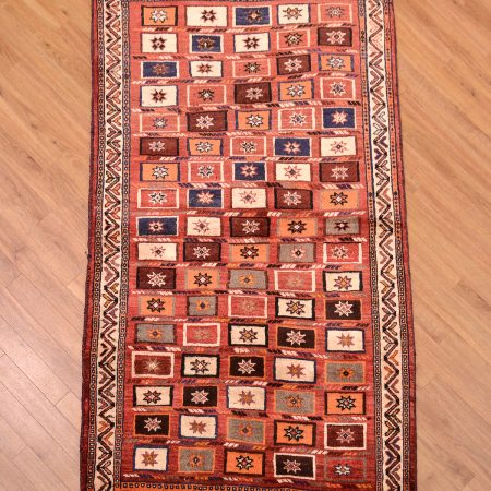Handmade tribal Persian Qashqai Gabbeh Rug with all over design of squares on a terracotta background.