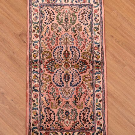 Fine hand-knotted Persian Sarouk Strip with traditional floral pattern on a salmon pink background.