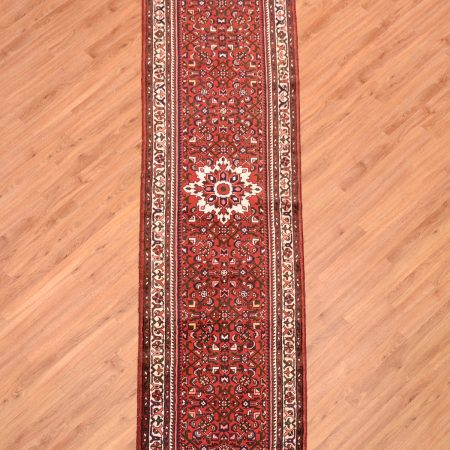 Handmade Persian Clearance Hamadan Runner with medallion design and terracotta field decorated with herati motifs.