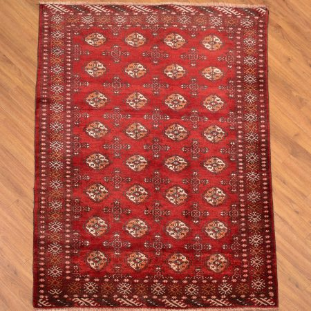 Red ground handknotted Persian Turkoman Rug with all over bokhara design consisting of 32 primary guls.