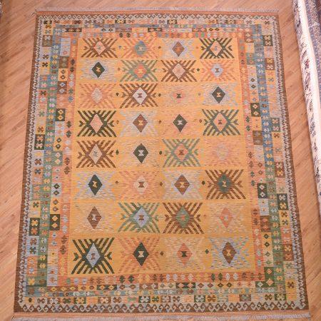 Handwoven Large Veg Dye Afghan Kilim / Kelim with an arrangement of 32 sunburst guls on a camel / gold background.