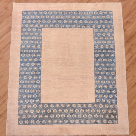 Chic handmade Pakistan Garous Modern Carpet with plain beige ground and inset blue border with floral decoration.