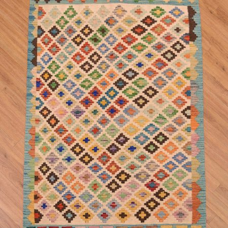 A funky handwoven Afghan Maimana Kilim Rug with all over design on a cream background surrounded by a turquoise border.