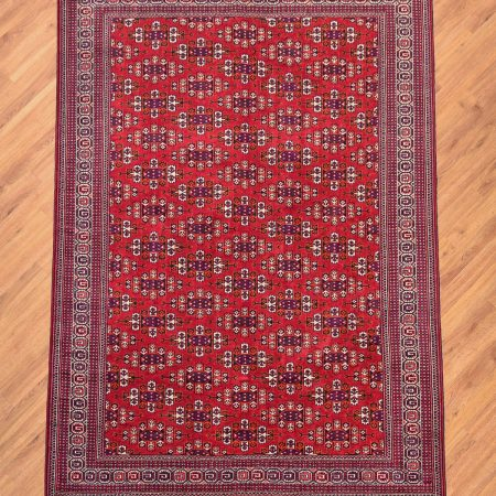 Traditional handmade Turkoman Yamoud Rug with all over design of guls on a red background.