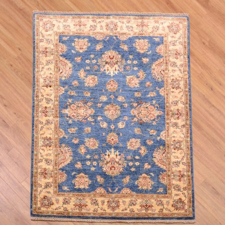 Handknotted Afghan Fine Ziegler Rug with blue field decorated with all over floral patterns surrounded by a beige/gold main border.