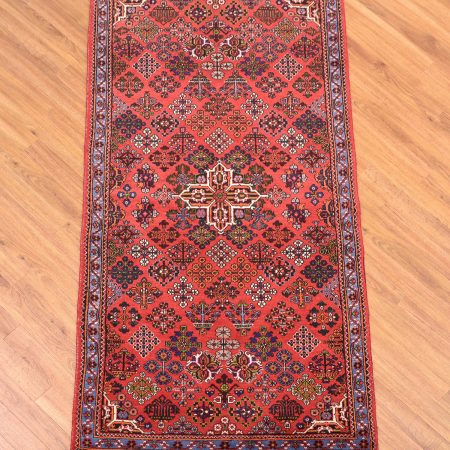 Handknotted Persian Meymeh Rug with a red field decorated with floral diamond shapes.