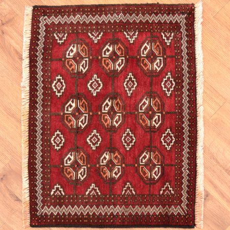 Fine Persian Belouch Mat with Bokhara design on a red background.