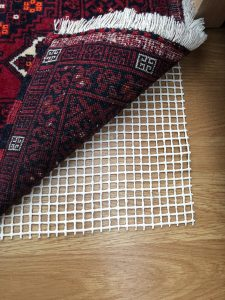 AKO Budget Anti-Slip Underlay laid on a laminate floor with Red Afghan Rug on top.