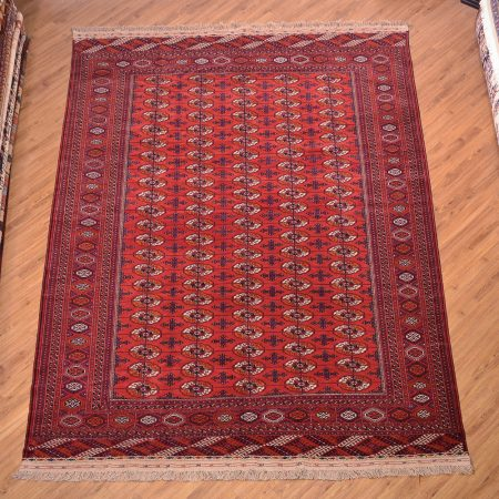 Traditional hand-knotted Turkoman Red Bokhara Carpet with all over design.