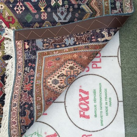 Foxi Rug Underlay in position to stop Qashquli Rug from moving on a green carpet.