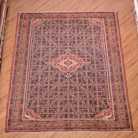 Handmade Persian Blue Hosseinabad Carpet with dark blue field, medallion centre surrounded by a field of herati motifs.