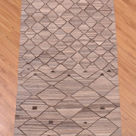 Handwoven Afghan Natural Dye Modern Kilim Rug with all over diamond pattern on a grey background.