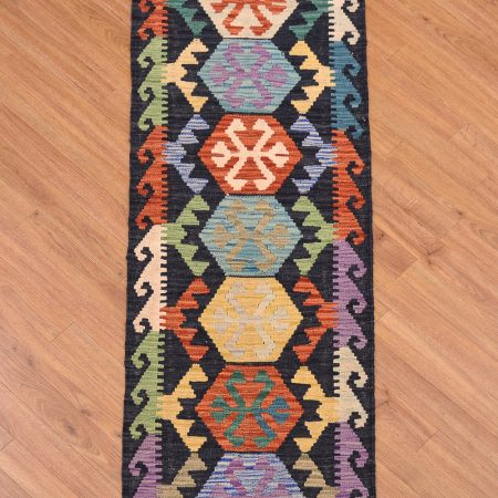 Eye-catching handwoven Afghan Kilim Strip with 7 medallion design conrasting with a black background.